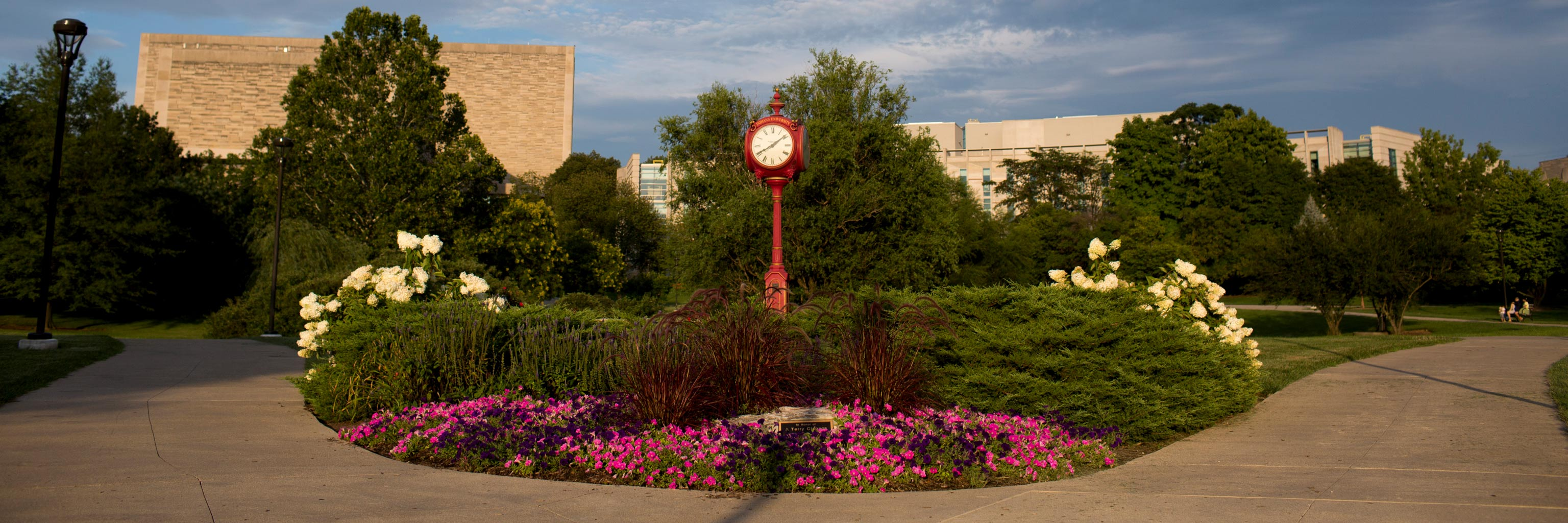 flowers, pathway, and decorative red clock