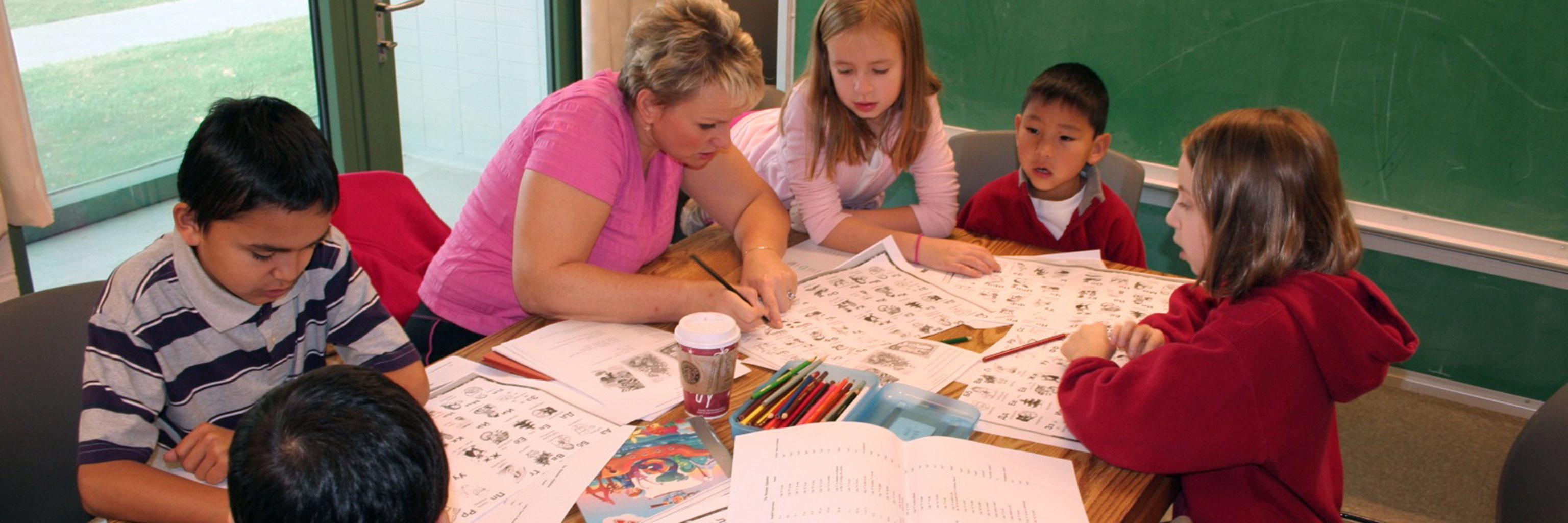 Teacher showing children coloring handouts in a classroom