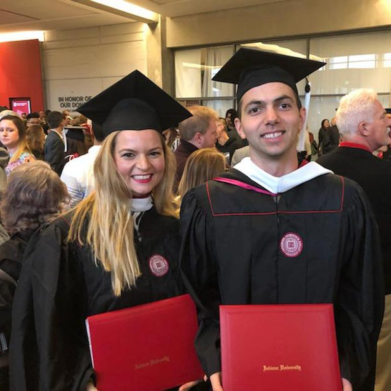 Two students smiling with graduation gowns