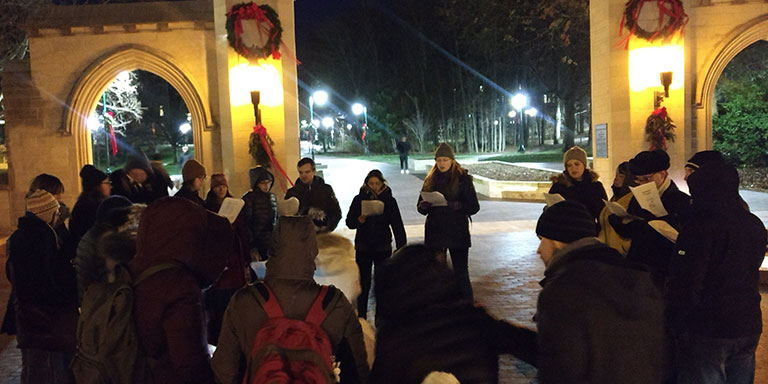 Students singing Christmas carols at the IU Sample Gates in winter